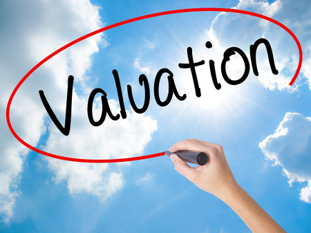 Woman Hand Writing Valuation with black marker on visual screen. Isolated on Sunny Sky. Business concept. Stock Photo