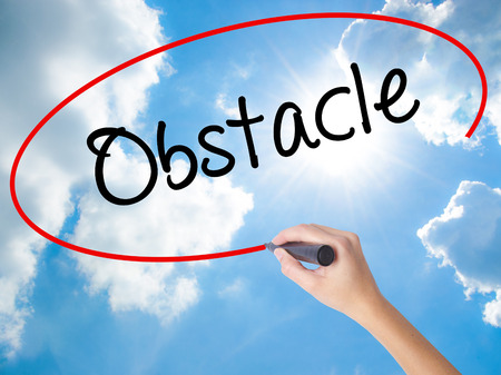 business obstacle: Woman Hand Writing Obstacle with black marker on visual screen. Isolated on Sunny Sky. Business concept. Stock Photo