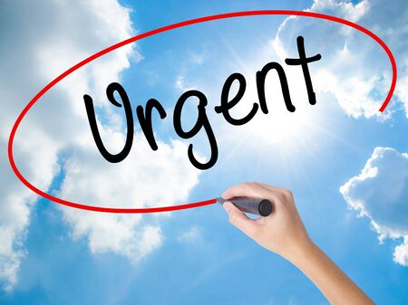 salient: Woman Hand Writing Urgent  with black marker on visual screen. Isolated on Sunny Sky. Business, technology, internet concept. Stock  Photo