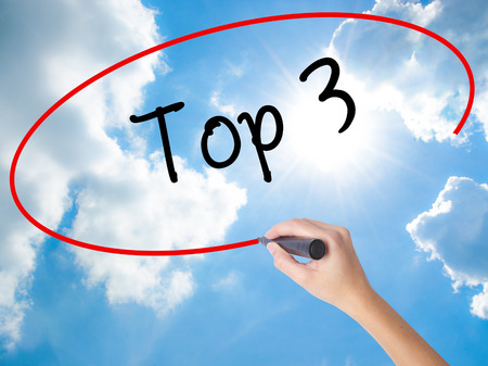 Woman Hand Writing Top 3 with black marker on visual screen. Isolated on Sunny Sky. Business, technology, internet concept.