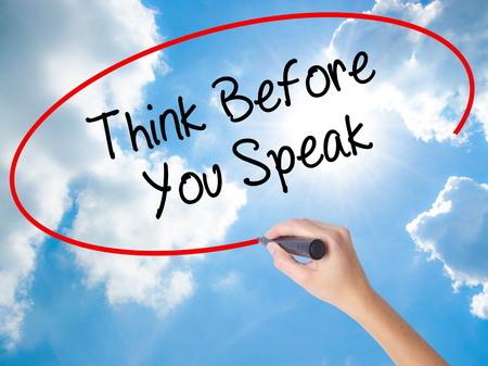 Woman Hand Writing Think Before You Speak with black marker on visual screen. Isolated on Sunny Sky. Business concept. Stock Photo