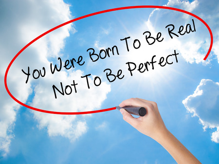 consistency: Woman Hand Writing You Were Born To Be Real Not To Be Perfect with black marker on visual screen. Isolated on Sunny Sky. Business, technology, internet concept. Stock Photo