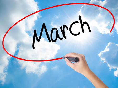 Woman Hand Writing March with black marker on visual screen. Isolated on Sunny Sky. Business concept. Stock Photo