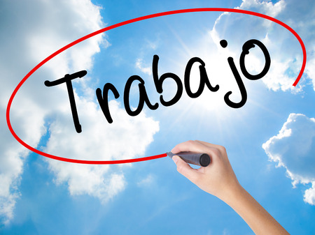 Woman Hand Writing Trabajo  (work in Spanish) with black marker on visual screen. Isolated on Sunny Sky. Business concept. Stock Photo