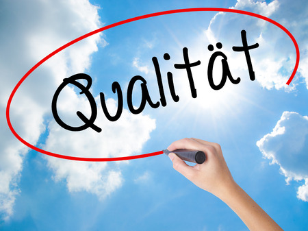 Woman Hand Writing Quality (Qualitat in German) with black marker on visual screen. Isolated on Sunny Sky. Business concept. Stock Photo