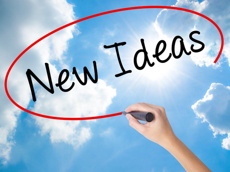 Woman Hand Writing New Ideas with black marker on visual screen. Isolated on Sunny Sky. Business concept. Stock Photo