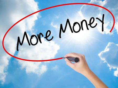 Woman Hand Writing More Money with black marker on visual screen. Isolated on Sunny Sky. Business concept. Stock Photo