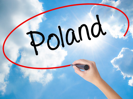 Woman Hand Writing Poland  with black marker on visual screen. Isolated on Sunny Sky. Business concept. Stock Photo