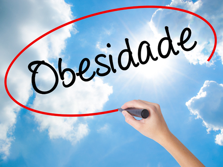Woman Hand Writing Obesidade (Obesity in Portuguese)  with black marker on visual screen. Isolated on Sunny Sky. Business concept. Stock Photo Stock Photo