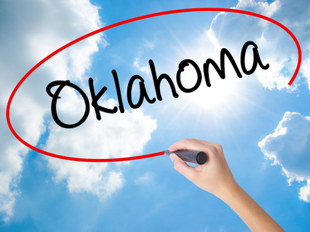 oklahoma: Woman Hand Writing Oklahoma with black marker on visual screen. Isolated on Sunny Sky. Business, technology, internet concept.