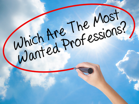 most talent: Woman Hand Writing Which Are The Most Wanted Professions? with black marker on visual screen. Isolated on Sunny Sky. Business concept. Stock Photo