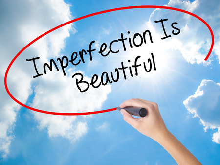 perfectionist: Woman Hand Writing Imperfection Is Beautiful with black marker on visual screen. Isolated on Sunny Sky. Business concept. Stock Photo Stock Photo