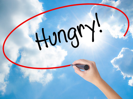 Woman Hand Writing Hungry! with black marker on visual screen. Isolated on Sunny Sky. Business concept. Stock Photo