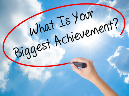 Woman Hand Writing What Is Your Biggest Achievement? with black marker on visual screen. Isolated on Sunny Sky. Business concept. Stock Photo Stock Photo