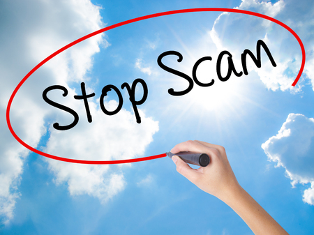 technology transaction: Woman Hand Writing Stop Scam with black marker on visual screen. Isolated on Sunny Sky. Business concept. Stock Photo