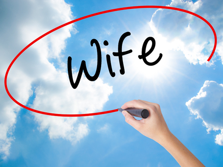 ex wife: Woman Hand Writing Wife with black marker on visual screen. Isolated on Sunny Sky. Business concept. Stock Photo