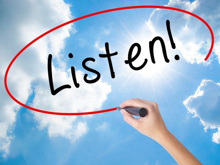 Woman Hand Writing Listen with black marker on visual screen. Isolated on Sunny Sky. Business concept. Stock Photo
