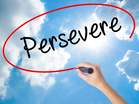 Woman Hand Writing Persevere with black marker on visual screen. Isolated on Sunny Sky. Business concept. Stock Photo