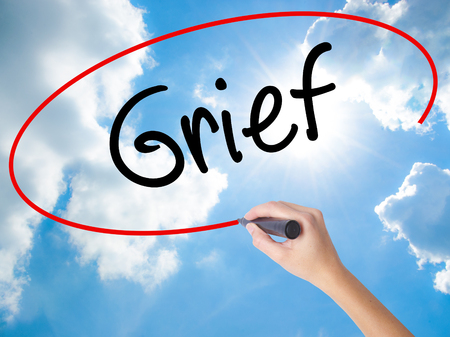 dolor: Woman Hand Writing Grief with black marker on visual screen. Isolated on Sunny Sky. Business concept. Stock Photo