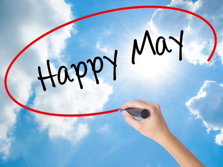 Woman Hand Writing Happy May with black marker on visual screen. Isolated on Sunny Sky. Business concept. Stock Photo