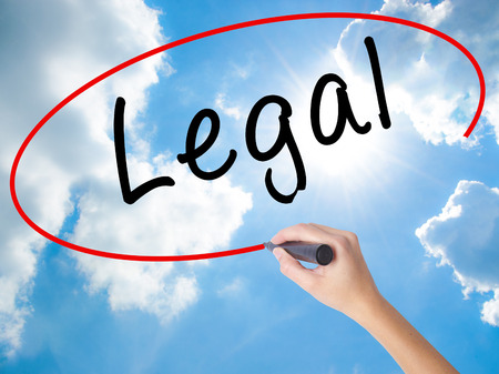 Woman Hand Writing Legal with black marker on visual screen. Isolated on Sunny Sky. Business concept. Stock Photo