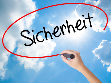 sicherheit: Woman Hand Writing Sicherheit (Safety in German) with black marker on visual screen. Isolated on Sunny Sky. Business,  internet concept. Stock Photo