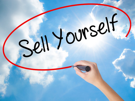 Woman Hand Writing Sell Yourself with black marker on visual screen. Isolated on Sunny Sky. Business concept. Stock Photo