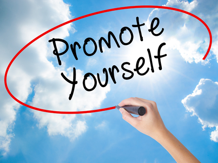 Woman Hand Writing Promote Yourself with black marker on visual screen. Isolated on Sunny Sky. Business concept. Stock Photo