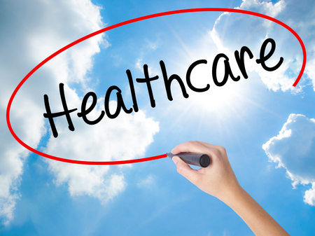 Woman Hand Writing Healthcare with black marker on visual screen. Isolated on Sunny Sky. Business concept. Stock Photo