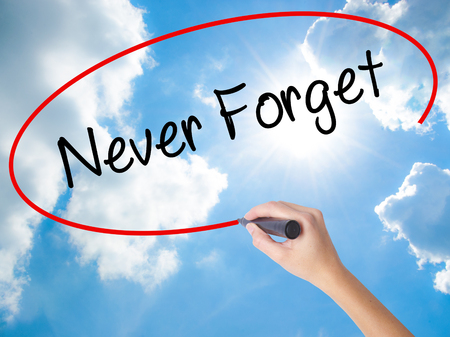 Woman Hand Writing Never Forget  with black marker on visual screen. Isolated on Sunny Sky. Business concept. Stock Photo