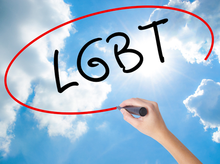 Woman Hand Writing LGBT Increase with black marker on visual screen. Isolated on Sunny Sky. Business concept. Stock Photo