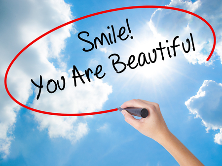 Woman Hand Writing Smile! You Are Beautiful with black marker on visual screen. Isolated on Sunny Sky. Business concept. Stock Photo
