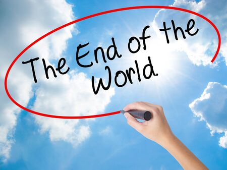 Woman Hand Writing The End of the World with black marker on visual screen. Isolated on Sunny Sky. Business concept. Stock Photo