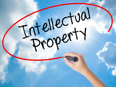 Woman Hand Writing Intellectual Property with black marker on visual screen. Isolated on Sunny Sky. Business concept. Stock Photo