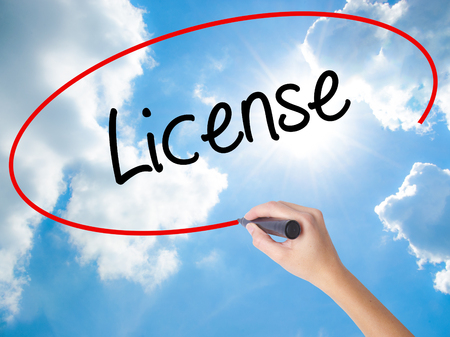 drivers license: Woman Hand Writing License with black marker on visual screen. Isolated on Sunny Sky. Business concept. Stock Photo