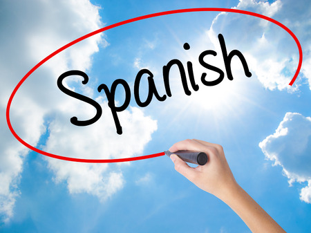 bilingual: Woman Hand Writing Spanish with black marker on visual screen. Isolated on Sunny Sky. Business concept. Stock Photo Stock Photo