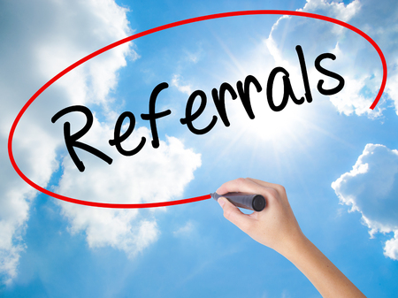 word of mouth: Woman Hand Writing Referrals with black marker on visual screen. Isolated on Sunny Sky. Business concept. Stock Photo Stock Photo
