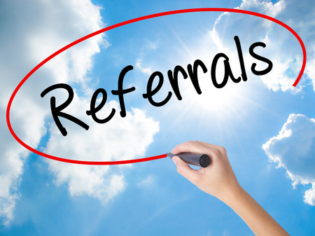 Woman Hand Writing Referrals with black marker on visual screen. Isolated on Sunny Sky. Business concept. Stock Photo Stock Photo