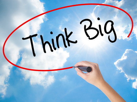 Woman Hand Writing Think Big with black marker on visual screen. Isolated on Sunny Sky. Business concept. Stock Photo