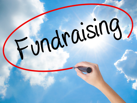 Woman Hand Writing Fundraising with black marker on visual screen. Isolated on Sunny Sky. Business concept. Stock Photo