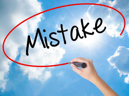 Woman Hand Writing Mistake with black marker on visual screen. Isolated on Sunny Sky. Business concept. Stock Photo