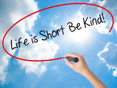 Woman Hand Writing Life is Short Be Kind! with black marker on visual screen. Isolated on Sunny Sky. Business concept. Stock Photo