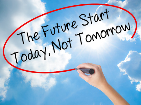 Woman Hand Writing The Future Start Today, Not Tomorrow with black marker on visual screen. Isolated on Sunny Sky. Business concept. Stock Photo