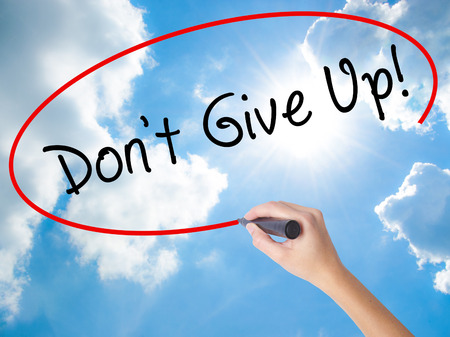 Woman Hand Writing Dont Give Up with black marker on visual screen. Isolated on Sunny Sky. Business concept. Stock Photo