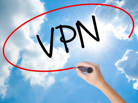 Woman Hand Writing VPN (Virtual Private Network) with black marker on visual screen. Isolated on Sunny Sky. Business concept. Stock Photo Stock Photo