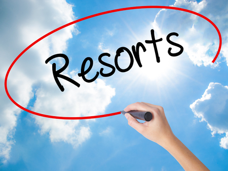 Woman Hand Writing Resorts  with black marker on visual screen. Isolated on Sunny Sky. Business concept. Stock Photo Stock Photo