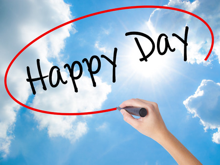 Woman Hand Writing  Happy Day with black marker on visual screen. Isolated on Sunny Sky. Business concept. Stock Photo Stock Photo