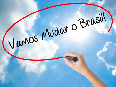 protestors: Woman Hand Writing Vamos Mudar o Brasil! (Lets Change Brazil in Portuguese)  with black marker on visual screen. Isolated on Sunny Sky. Business concept. Stock Photo Stock Photo
