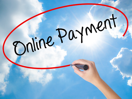 technology transaction: Woman Hand Writing Online Payment with black marker on visual screen. Isolated on Sunny Sky. Business concept. Stock Photo