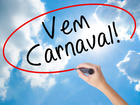 Woman Hand Writing Carnival is Coming (in Portuguese) with black marker on visual screen. Isolated on Sunny Sky. Business concept. Stock Photo